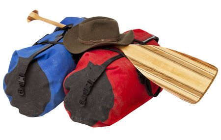 canoe paddle: paddling trip or vacation concept - wooden canoe paddle, waterproof duffels dirty by river mud and hat isolated on white