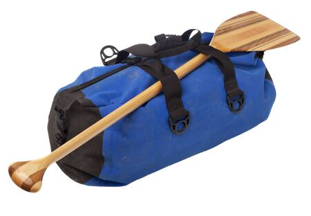 canoe paddle: paddling trip or vacation concept - wooden canoe paddle and waterpoof duffel with river mud stains, isolated on white