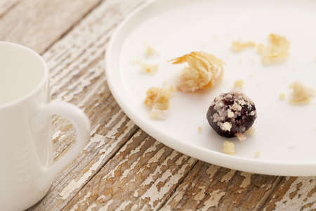 dessert gone - crumbs of cherry cheese danish pastry on white plate with espresso coffee cup on grunge wood table Stock Photo - 9157434