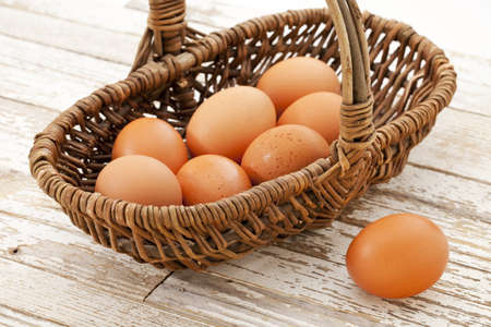 basket of brown chicken eggs against grunge wooden table with white peeling off paint Stock Photo - 9157466