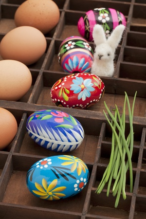 typesetter: Easter decoration concept - brown chicken eggs, painted eggs with floral motif, green chive and woolen bunny in a vintage drawer (shadow box)