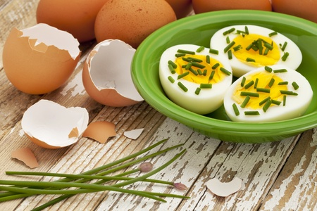 boiled chicken eggs with green chive against grunge wood surface - Easter or spring concept photo