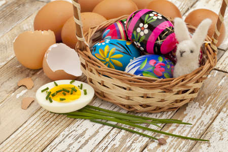 Easter decoration concept - painted Easter eggs, chicken eggs with green chive and woolen bunny in a basket against grunge wooden surface photo