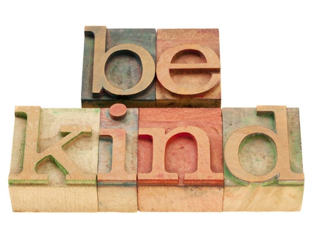 kind: be kind motivational reminder - phrase in vintage wood letterpress type, stained by color inks, isolated on white