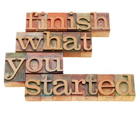 slogan: terminar lo empez� - lema motivacional en bloques de impresi�n tipogr�fica cosecha de madera, aislados en blanco