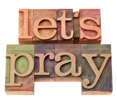 spiritual concept - let us pray phrase in vintage wood letterpress type, stained by color inks, isolated on white Stock Photo - 9215225