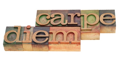 Enjoy life before it is too late, existential cautionary Latin phrase - Carpe Diem  in vintage wood letterpress type, stained by color inks, isolated on white Stock Photo