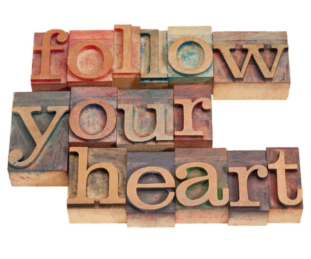 letterpress  type: follow your heart phrase in vintage wood letterpress type, stained by color inks, isolated on white