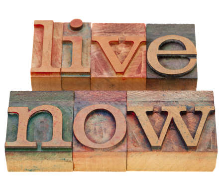 live now reminder in vintage wood letterpress type, stained by color inks, isolated on white Stock Photo - 9261506