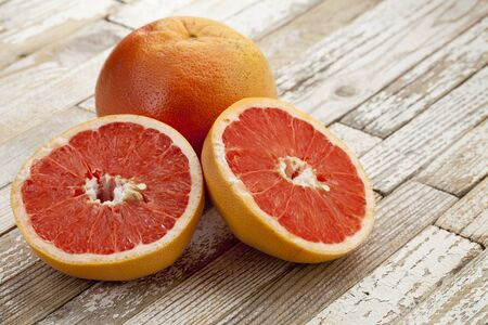red cut grapefruit on white grunge wood table with paint peeling off Stock Photo - 9283784