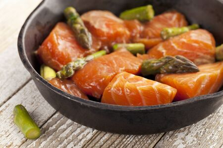 salmon and asparagus stir fry in tamari sauce ready for cooking on iron pan Stock Photo - 9283780