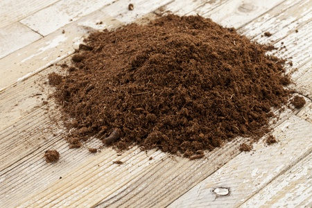 turba: Canadiense de turba de sphaigne utilizado como suelo acondicionado en jardiner�a, una peque�a pila en una superficie de madera grunge