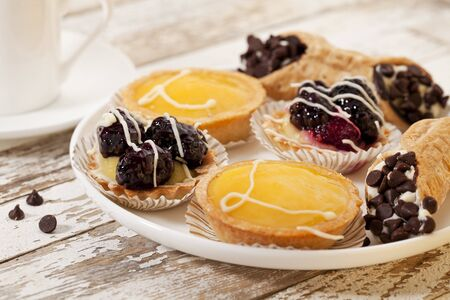 plate of fruit mini tarts and coffee on a rustic wooden table Stock Photo - 9335149
