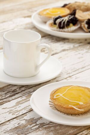 lemon mini tart and espresso coffee on a rustic wooden table Stock Photo - 9335151