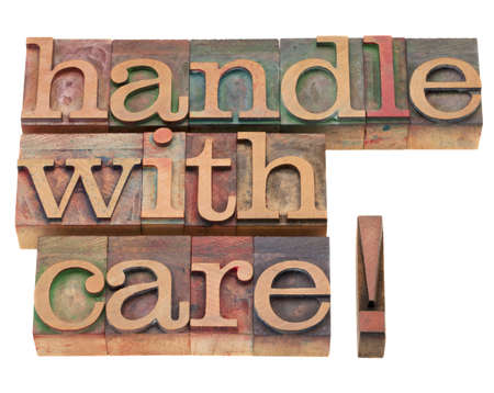 letterpress letters: handle with care warning in vintage wood letterpress printing blocks, isolated on white
