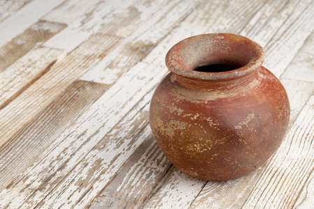 small red and brown clay plant pot (mass produced planter) with rough, grunge finish,  on white wood background Stock Photo - 9387538