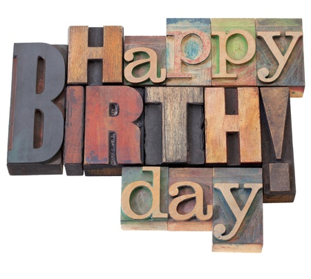 letterpress words: Happy Birthday in antique wood letterpress printing blocks, isolated on white
