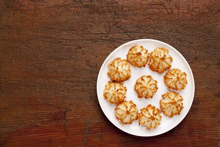 top: plate of coconut macaroon cookies on old scratched wooden table, top view