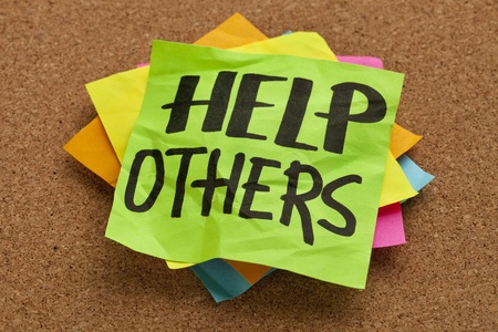 help others reminder on sticky note posted on a cork board Stock Photo - 9503949