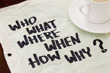 when: what, when, where, why, how, who questions - black marker handwriting on a grid paper with a coffee cup