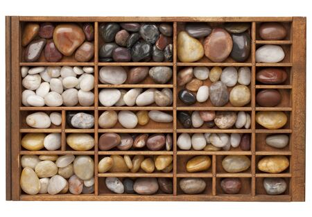typesetter: colorful river pebbles in vintage wood typesetter drawer isolated with clipping path Stock Photo