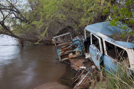 consumerism and environment concept - junk wreck cars on the river shore (South Platte in Colorado) Stock Photo