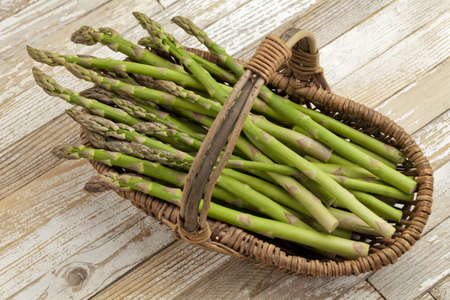 green asparagus in  wicker basket on grunge white painted wood background Stock Photo - 9614092