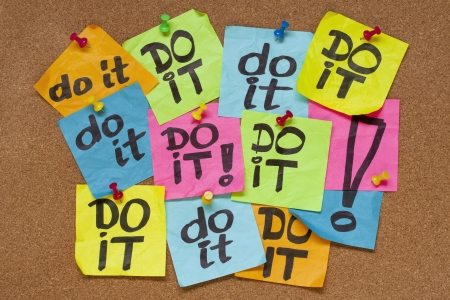 note of exclamation: fighting procrastination concept - do it phrase on color sticky notes posted on a cork bulletin board