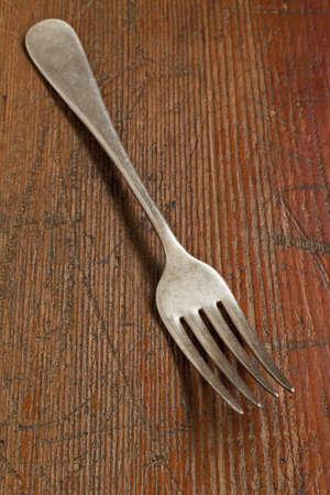 scratched: vintage fork on scratched grunge wood surface