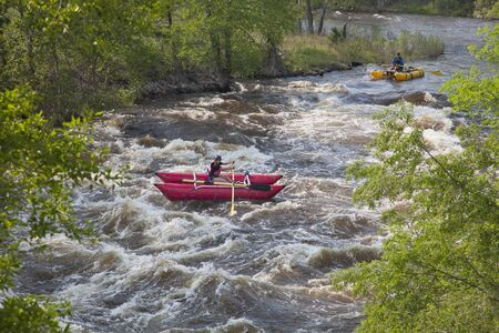 FORT COLLINS, COLORADO, USA - JUNE 4, 2011: Two white water catarafts floating over Maddog Rapid on Cache la Poudre River west of Fort Collins, Colorado as the snow pack in the high country begins to melt. Fort Collins, Colorado, June 4, 2011. Stock Photo - 9656863