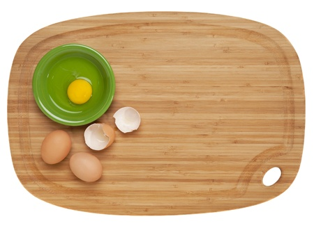 food preparation concept - broken eggs and ceramic bowl on bamboo cutting board, isolated on white Stock Photo - 9739560