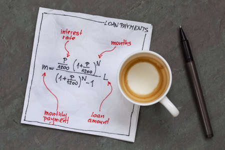 loan payment equation sketched on a white cocktail napkin with empty coffee cup on a slate stone table Фото со стока