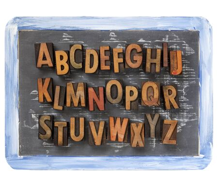 letterpress type: English alphabet - vintage wood letterpress printing blocks on a small slate blackboard with chalk texture and rough blue frame