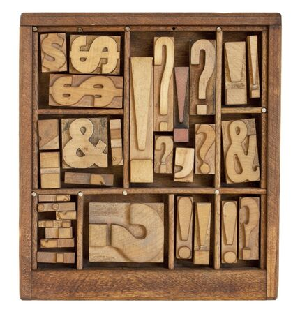 typesetter: question mark, exclamation point, ampersand, and other punctuation symbols - vintage letterpress printing blocks in small wooden typesetter box with dividers, isolated on white