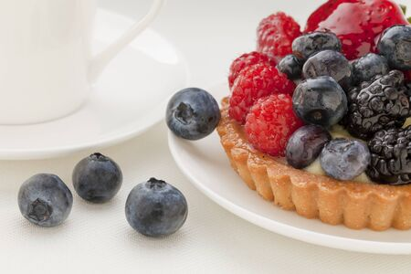 fruit tart with blueberry, blackberry, raspberry and strawberry, a coffee cup in background Stock Photo - 9739583