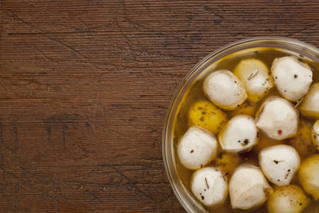 balls of mozzarella cheese marinated in oil with seasoning, glass bowl on weathered wood background Stock Photo - 9834205