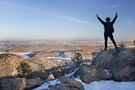 silhouette of happy male hiker standing on a rock and looking down to Horsetooth Reservoir, town of Fort Collins and Colorado plains, typical hazy winter scenery Banco de Imagens
