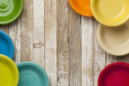 copy space on a grunge white painted  wood table surrounded by color ceramic bowls photo