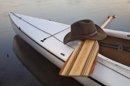 a cowboy hat,a wooden paddle across cockpit of decked expedition canoe