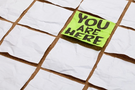 here: you are here concept - handwriting on a green sticky note surrounded by blank white ones Stock Photo