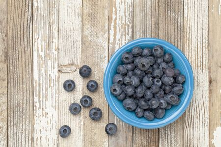 blueberries in a blue ceramic bowl on a grunge white painted wood surface Stock Photo - 10318139