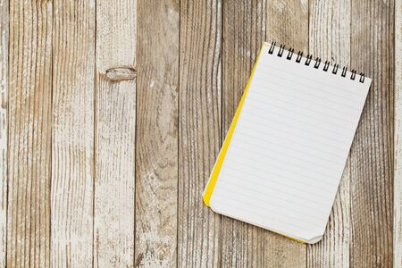 a small lined notebook on a rustic grunge wooden table Stock Photo - 10318140