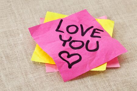 office romance: office romance concept - love you text handwritten on red sticky note