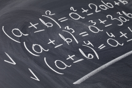 mathematical education concept - algebra equations handwritten with white chalk on blackboard