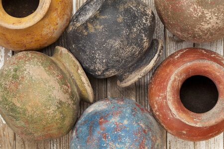clay pots (planters) with a color grunge finish on wooden surface Stock Photo - 10444327