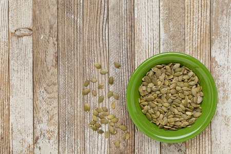 pumpkin seeds in a green ceramic bowl on grunge white painted wood table Stock Photo - 10652672