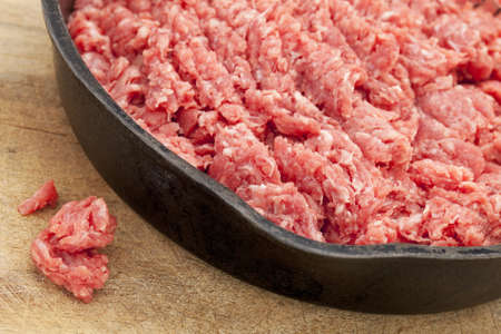 raw ground bison (buffalo)  meat on an iron pan against wood surface Stock Photo - 10684346
