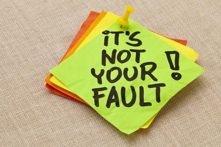 note of exclamation: Motivaci�n concepto - No es tu culpa exclamaci�n - escritura a mano en una nota verde pegajosa contra tablero de la lona