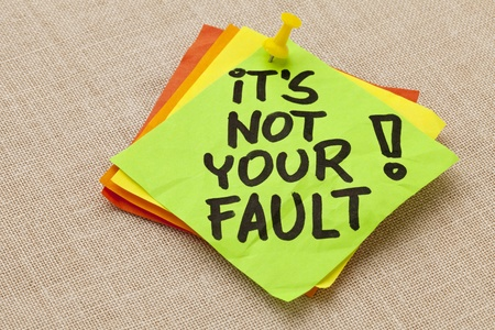note of exclamation: Motivational concept - It is not your fault exclamation  - handwriting on a green sticky note against canvas board