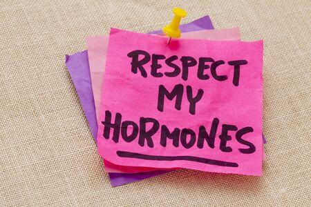 hormonas: respetar a mis hormonas humourous aviso - escritura a mano en una nota de color púrpura pegajosa contra tablero de la lona Foto de archivo